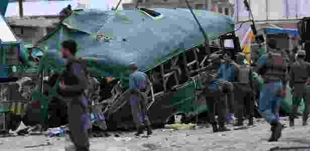 Policiais afegãos observam destroços de ônibus em local de atentado nos arredores de Cabul, no Afeganistão - Wakil Kohsar/AFP