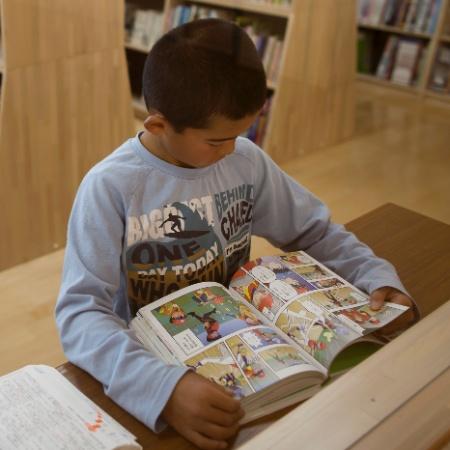Criança lê uma história em quadrinhos em uma biblioteca do Japão - TOMOHIRO OHSUMI/NYT