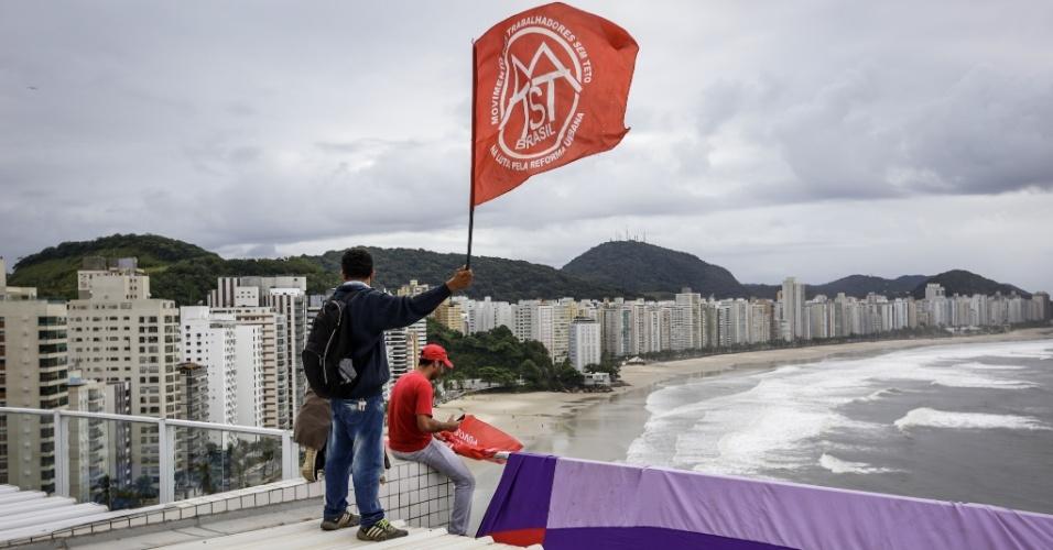16.abr.2018 - Enquanto um grupo de manifestantes gritam palavras de ordem em frente ao prédio que fica em frente para a praia de Astúrias, no Guarujá (SP), outro grupo conseguiu subir na cobertura de onde erguem bandeiras do MTST e faixas da Frente Povo Sem Medo