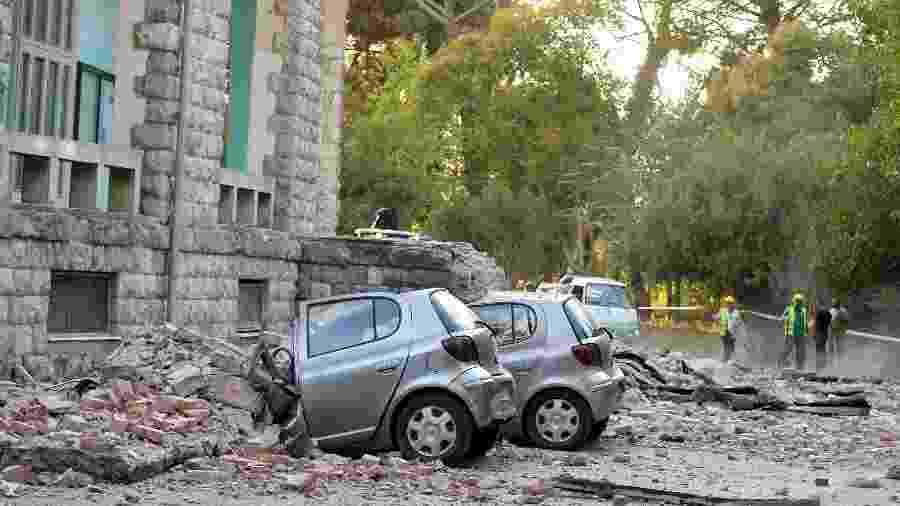 Carros esmagados por escombros na cidade de Tirana, na Albânia - GENT SHKULLAKU / AFP