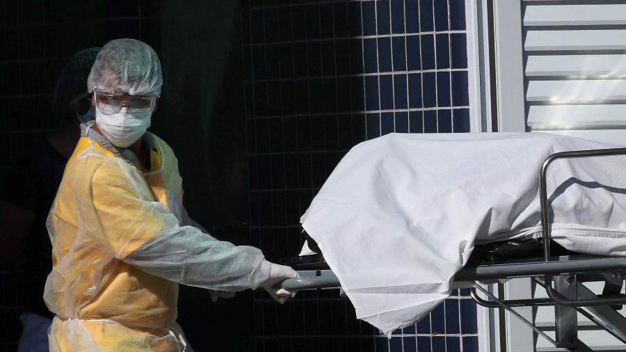 Profissional de saúde com roupa de proteção remove corpo para caminhão refrigerado em hospital do Rio de Janeiro - RICARDO MORAES