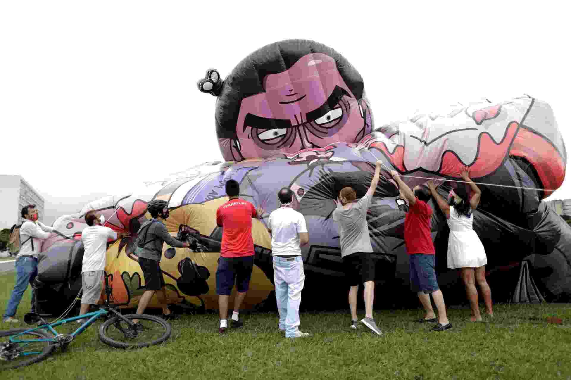 21.fev.2021 - Manifestantes enchem boneco inflável o presidente Jair Bolsonaro em protesto contra o governo em Brasília - REUTERS/Ueslei Marcelino