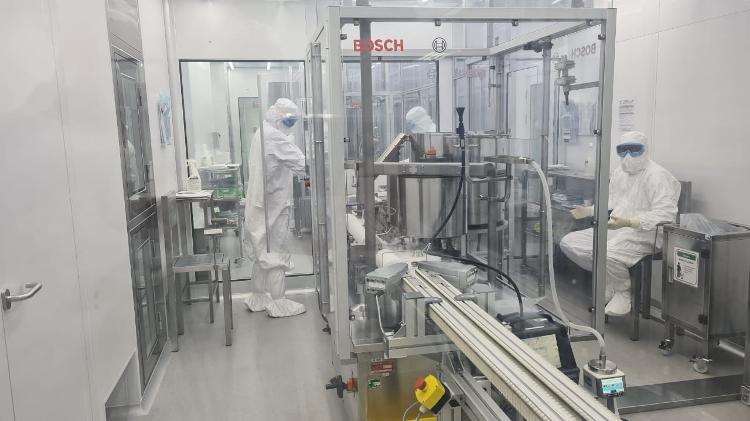 19.02.2021 - Dupla de cientistas ficam em sala isolada acompanhando a máquina que tampa os frascos da CoronaVac - Leonardo Martins/UOL - Leonardo Martins/UOL