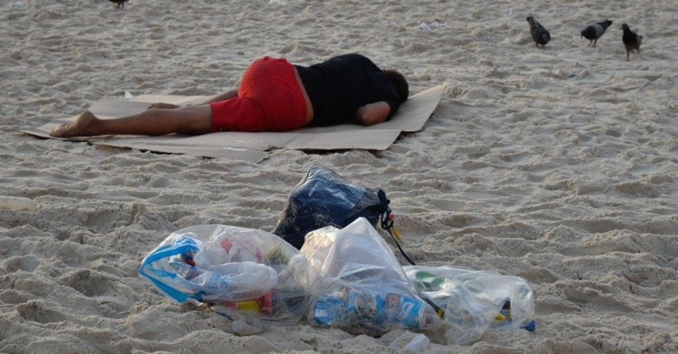 1º.jan.2016 - Homem dorme ao lado de sacos de lixo deixados na areia da praia de Copacabana, na zona sul do Rio de Janeiro, na manhã do primeiro dia de 2016, após a tradicional festa de Réveillon