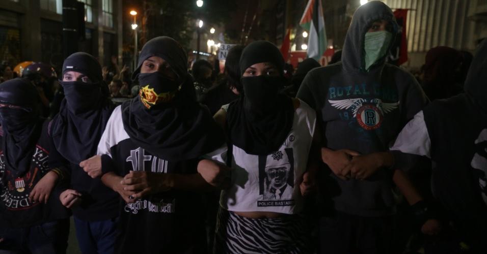 21.jan.2016 - Com os rostos cobertos, manifestantes fazem passeata nas ruas do centro de São Paulo durante quinto ato convocado pelo MPL (Movimento Passe Livre) contra o aumento das passagens de ônibus e metrô da capital paulista. O protesto teve início do Terminal Parque Dom Pedro 2º