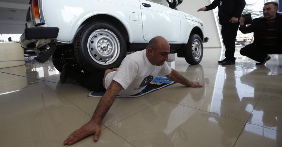 16.fev.2016 - Norik Yajian aguarda a passagem de um carro em cima do seu corpo em Tbilisi, Geórgia. Yajian pretende deixar quatro carros passarem sobre ele para tentar quebrar um recorde mundial do Guinness