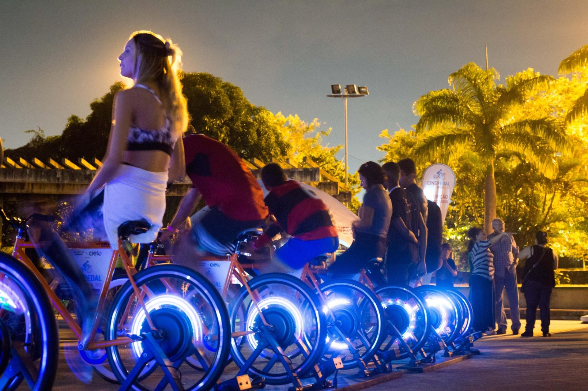 21.mai.2016 - Pessoas pedalam para gerar energia elétrica durante a primeira edição do Cine Pedal Brasil,na Lagoa Rodrigo de Freitas, no Parque dos Patins, Rio de Janeiro. Com objetivo de incentivar a mobilidade, o projeto ocupa praças públicas exibindo filmes projetados a partir da energia gerada por meio de bicicletas