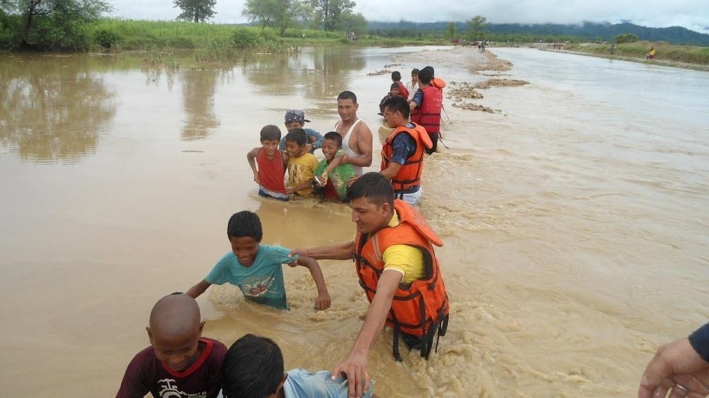 27.jul.2016 - Polícia orienta crianças para chegarem até um barco e saírem da enchente em Bardiya, no Nepal. Ao menos 33 pessoas morreram e 23 estão desaparecidas devido às enchentes e deslizamentos de terra provocados por fortes chuvas na região