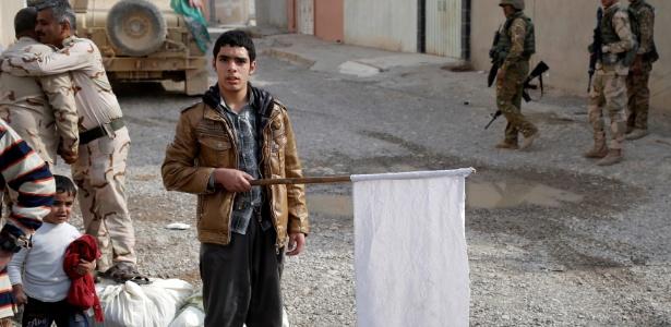Jovem segura uma bandeira branca diante de soldados iraquianos em Mossul