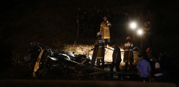Policiais analisam peças de helicóptero da PM que caiu no Rio de Janeiro, no sábado, matando quatro oficiais