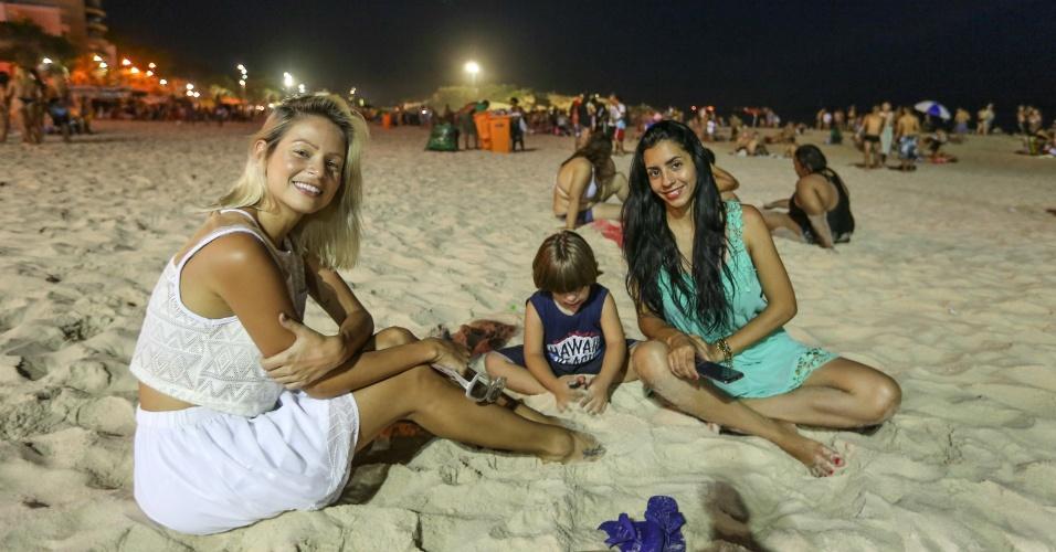 """27.dez.2016 - Para fugir do sol forte durante o dia, Luana de Lima (de branco) levou a amiga Danila Seixas (de verde) e seu filho, Miguel, para a praia do Arpoador à noite. """"100% seguro não é, mas é mais agradável"""", comentou Luana"""