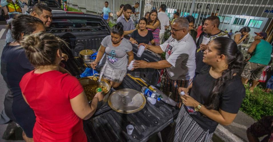 3.jan.2017 - Voluntários levam sopa para distribuir aos parentes dos mortos na rebelião do presídio Anísio Jobim, que esperam notícias em frente ao IML (Instituto Médico Legal) de Manaus