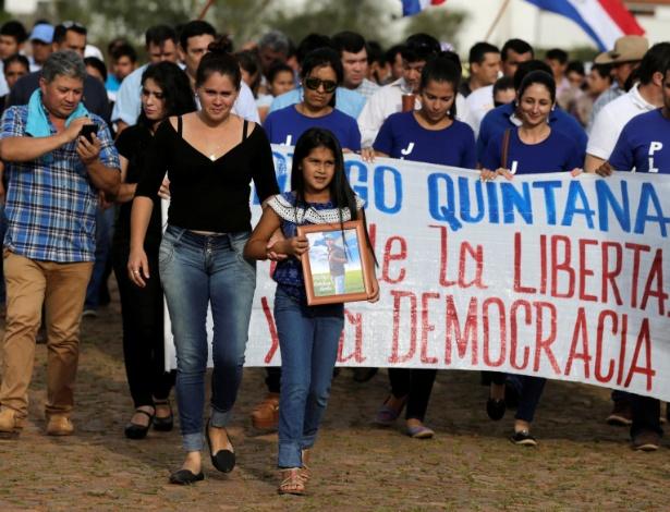 Luz, filha de Rodrigo Quintana, carrega foto do pai durante funeral em La Colmena (Paraguai)