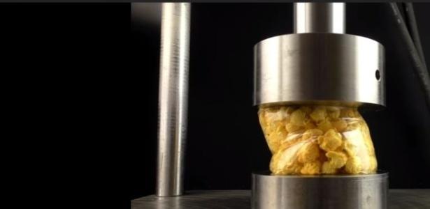 O que acontece quando um pacote pipoca é colocado em uma prensa hidráulica - YouTube/reprodução