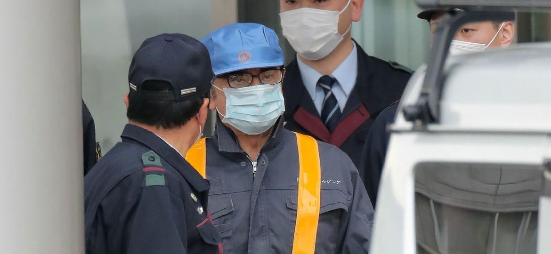 Carlos Ghosn saiu da prisão vestindo um uniforme, máscara e boné - Jiji Press/AFP