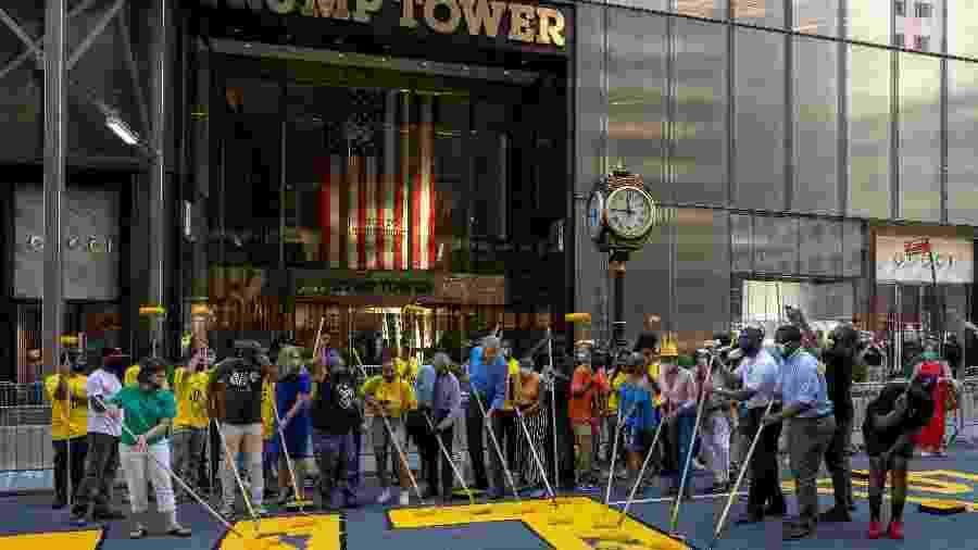 O prefeito de Nova York, Bill De Blasio (ao centro, de camisa azul), participa de mutirão na principal avenida da cidade - Getty Images