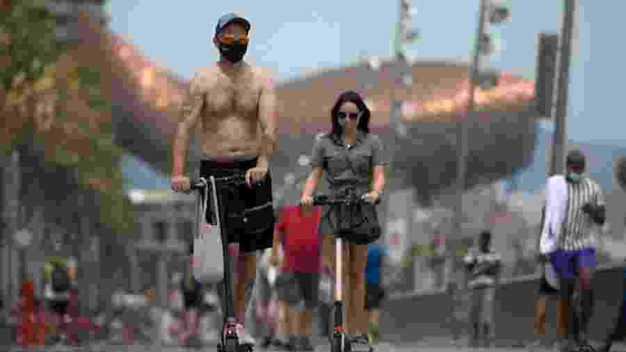 De máscara, moradores andam de patinete próximo à praia de Barceloneta, em Barcelona, na Espanha - Lluis Gene/AFP
