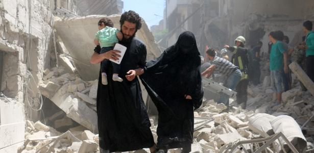 28.abr.2016 - Família anda no meio de edifícios destruídos após bombardeio em Aleppo