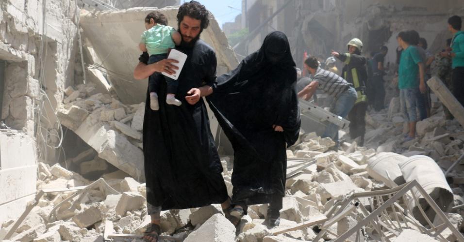 28.abr.2016 - Família anda no meio dos escombros de edifícios destruídos durante bombardeiro em Aleppo, Síria. Pelo menos 27 pessoas morreram, entre elas o último pediatra que havia na região controlada pelos rebeldes