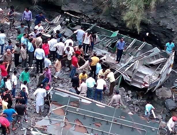 21.mai.2016 - Curiosos se reúnem ao lado dos destroços de ônibus que caiu em um desfiladeiro no norte do estado indiano de Himachal Pradesh. A queda causou a morte de pelo menos 14 pessoas, e deixou 31 feridos. Nas últimas 24 horas, este acidente e outro, na região montanhosa somaram 30 vítimas fatais