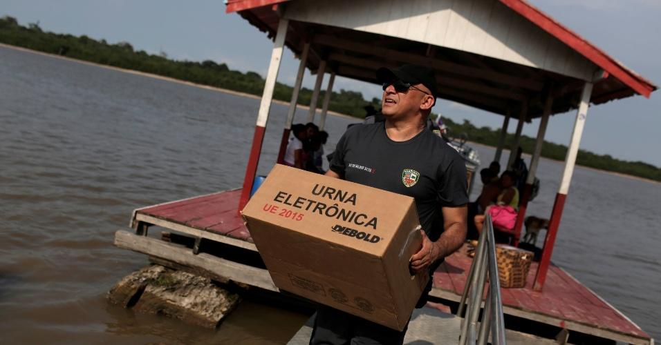 Policial carrega caixa com urna eletrônica em uma comunidade de ribeirinhos, à margem do Rio Negro, em Manaus