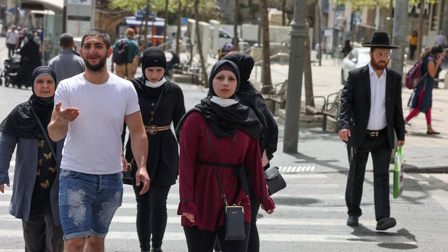 Pessoas caminham em rua de Jerusalém após autoridades israelenses anunciarem que máscaras não são mais necessárias ao ar livre - Menahem Kahana/AFP