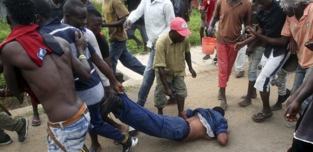 Homens arrastam policial acusada de disparar contra um manifestante em Bujumbura