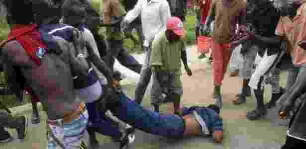 Homens arrastam policial acusada de disparar contra um manifestante em Bujumbura - Goran Tomasevic/Reuters