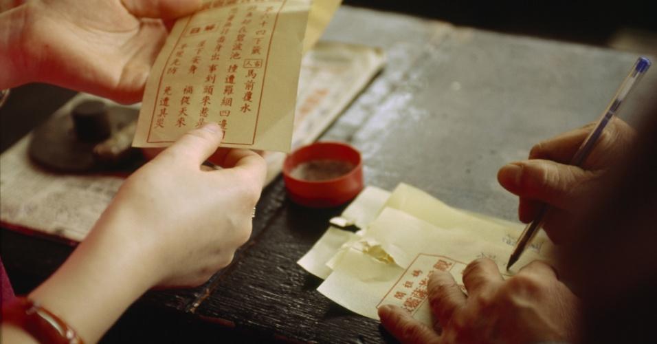 O que o futuro reserva? Uma mulher recebe dicas sobre seu futuro de um adivinho no templo de A-Má, em Macau