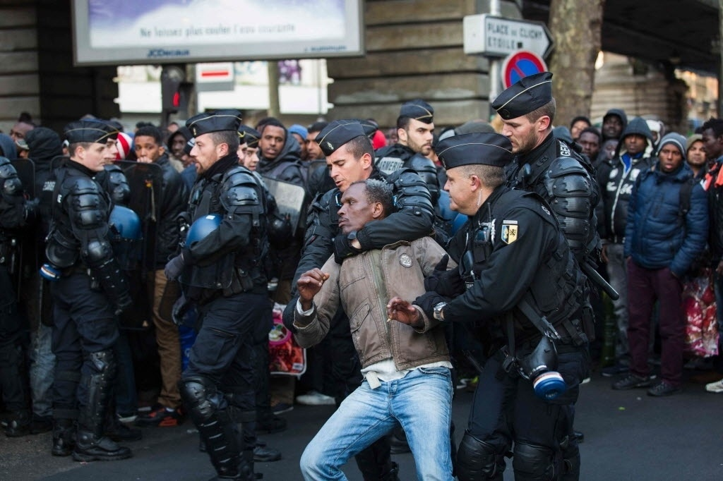 2.mai.2016 - Policiais franceses prendem um homem durante o fechamento de um acampamento improvisado sob a estação de metrô Stalingrado, em Paris, na França. Cerca de 1.615 imigrantes moravam no local. A polícia afirma que todos os moradores do acampamento foram encaminhados para abrigos