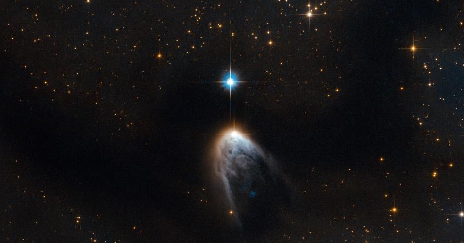 """""""VÉU"""" COBRE ESTRELA RECÉM-NASCIDA - Foto mostra estrela jovem a 2.280 anos-luz da Terra. A imagem, feita pelo telescópio Hubble, é a combinação de dois comprimentos de onda: o espectro visível (luz azul) e a radiação infravermelha (laranja). A parte branca na foto ocorre porque as estrelas nascem no fundo de densas nuvens de poeira e gás. Essa especificamente nasceu no Complexo de Nuvens Moleculares Circinus"""