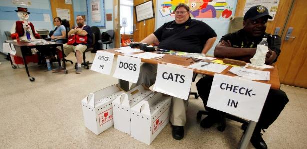 Policiais e funcionários da Cruz Vermelha esperam por moradores e seus animais em abrigo em uma escola primária em North Charleston, na Carolina do Sul