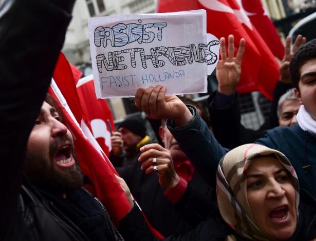 """Manifestantes com bandeiras turcas e um cartaz que diz """"Holanda fascista"""" protestam diante do Consulado holandês em Istambul (Turquia)"""