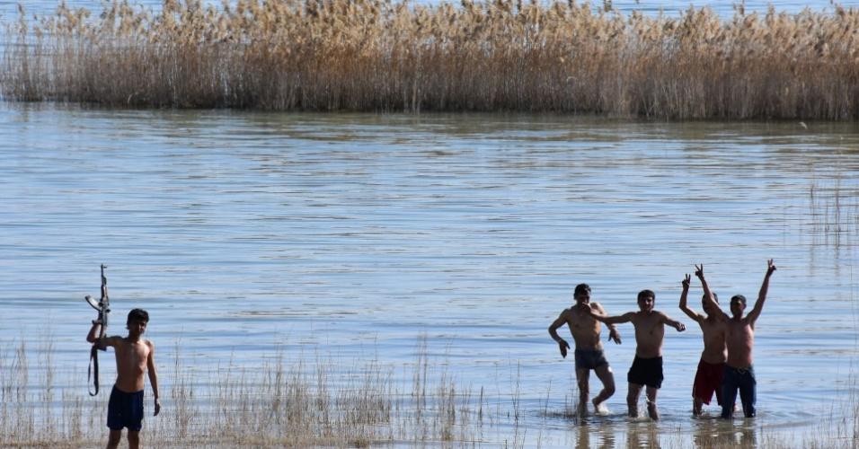 Soldados das forças do governo sírio brincam no lago Assad, perto de uma estação de bombeamento de água retomada dos rebeldes nos arredores de Aleppo, próximo da cidade de Al-Khafsah