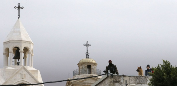 24.dez.2017 - Guarda palestino em frente à Basílica da Natividade, em Belém