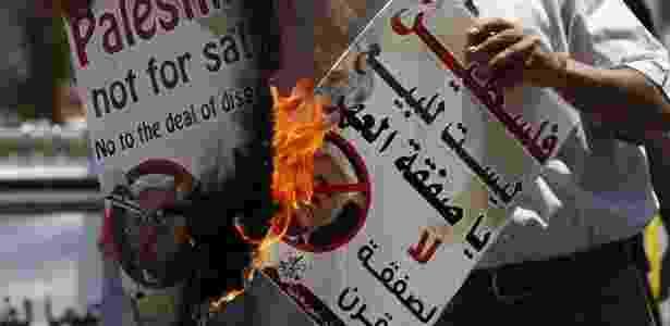 02.jul.2018 - Palestinos queimam retratos do presidente norte-americano Donald Trump, em protesto contra os apoios dados à Israel - AFP