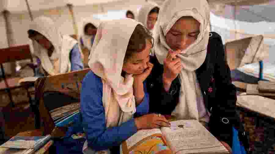 Estudantes compartilham livro didático durante as aulas em uma das tendas da Rustam School, em Yakawlang, no Afeganistão - Jim Huylebroek/The New York Times