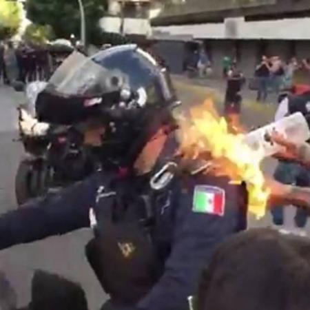 Policial é surpreendido por manifestante, pelas costas, no México - Reprodução/El Universal