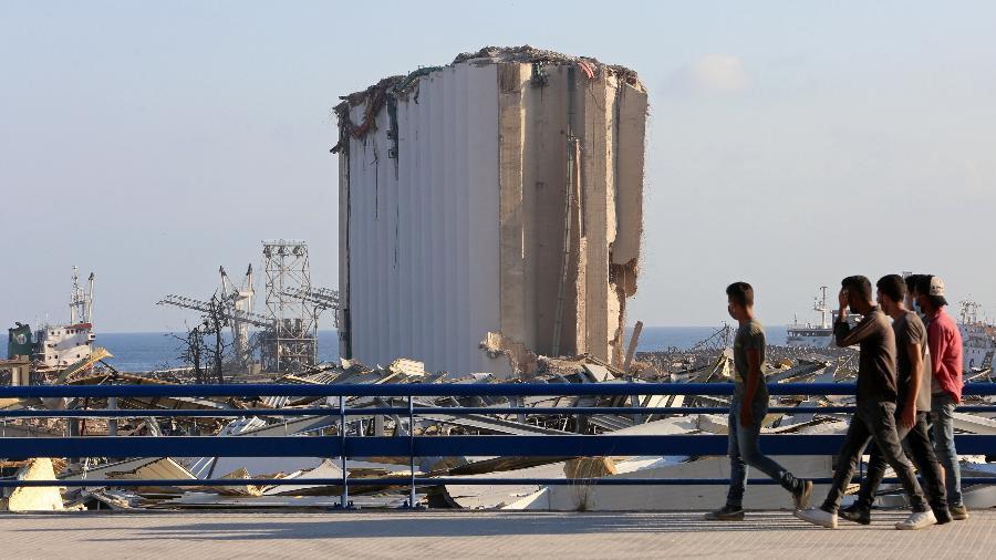 Pessoas andam próximo ao local da explosão em Beirute, na área portuária da capital do Líbano - REUTERS/Aziz Taher