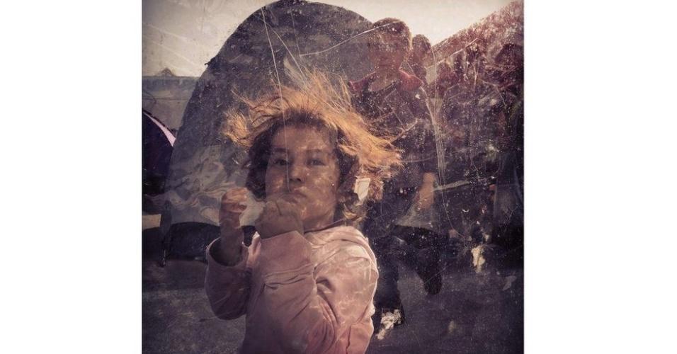 """A foto de uma pequena refugiada afegã brincando em um campo do porto de Piraeus, em Atenas, venceu a categoria """"Notícias/Eventos"""". A imagem foi registrada por Loulou d'Aki, da Suécia, em março de 2016"""