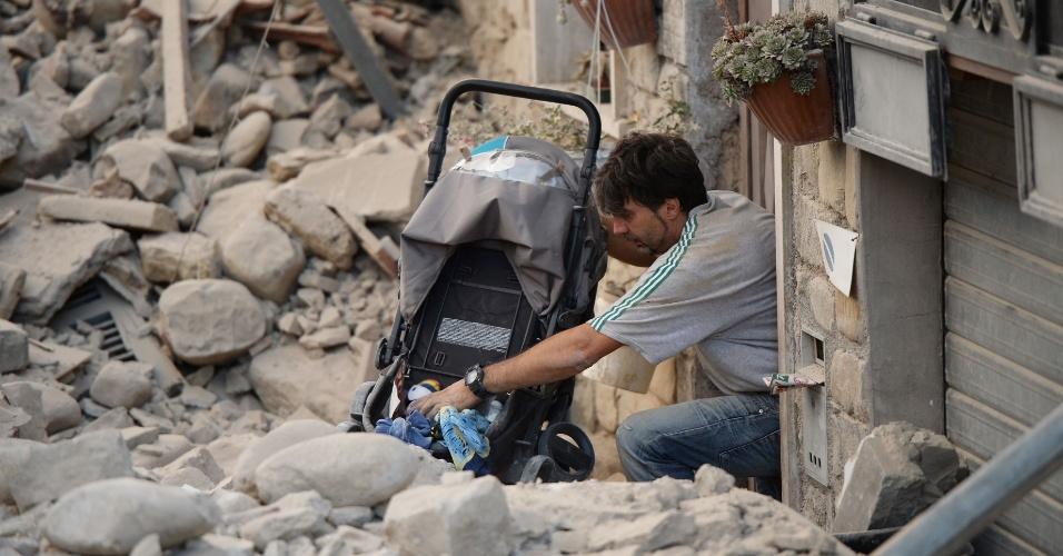 24.ago.2016 - Um homem empurra um carrinho de criança entre os edifícios danificados após um forte terremoto que atingiu a região central da Itália. O incidente deixou dezenas de mortos e feridos