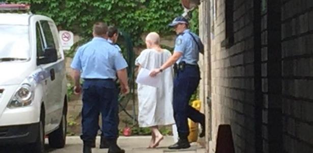 John Walsh (de branco) é conduzido por policiais após ser acusado de matar o companheiro de cela