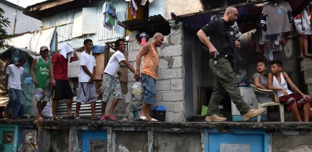 Agente antidrogas (dir) das Filipinas leva suspeitos durante busca em favela em Manila
