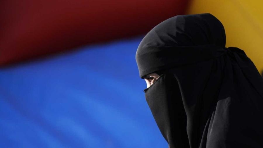 Mulher usa nicabe, o véu islâmico que só deixa visível a região dos olhos - Michael Buholzer/REUTERS