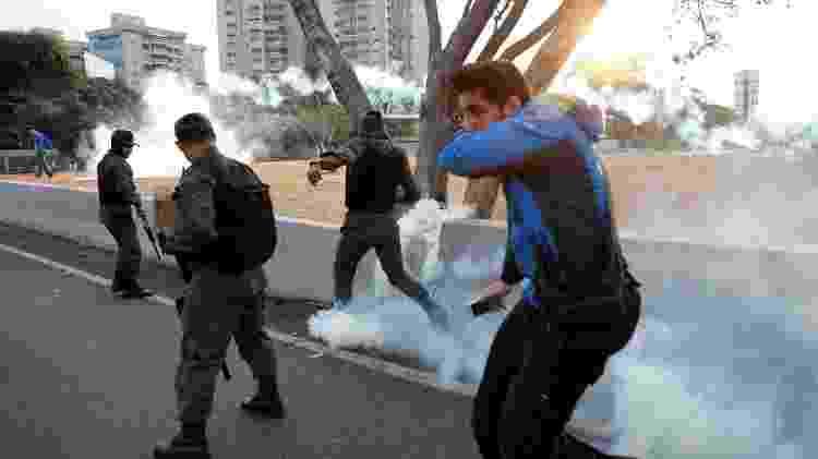 Militares que apoiam a oposição reagem a gás lacrimogêneo atirado contra eles em área militar em Caracas, capital do país - Carlos Garcia Rawlins/Reuters - Carlos Garcia Rawlins/Reuters