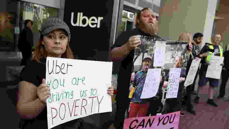 Motoristas de Uber e Lyft levantam cartazes em protesto na matriz do Uber, em San Francisco, Califórnia - Justin Sullivan/Getty Images/AFP