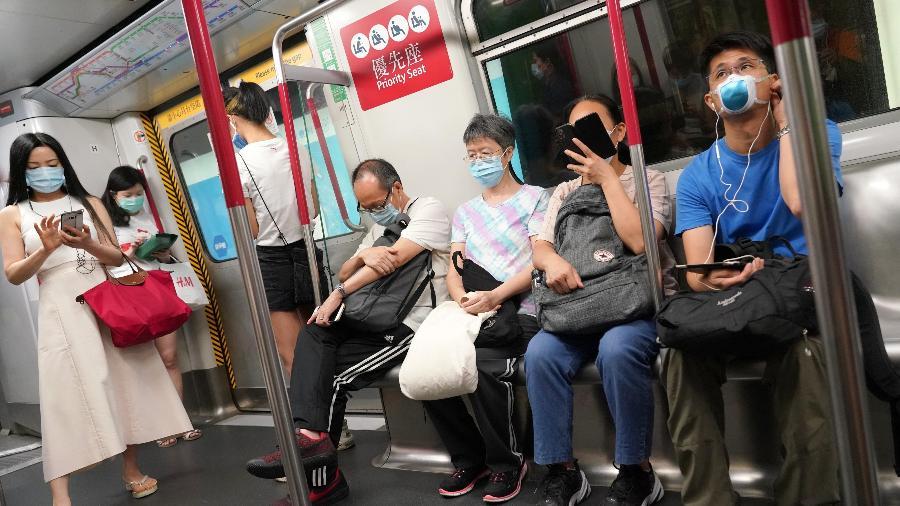 Pessoas com máscara em trem de Hong Kong, na China, durante a pandemia do coronavírus - Getty Images