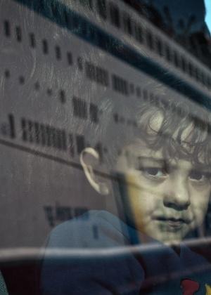 Menino refugiado olha para fora do ônibus, após desembarcar de uma balsa no porto de Pireu, em Atenas, Grécia