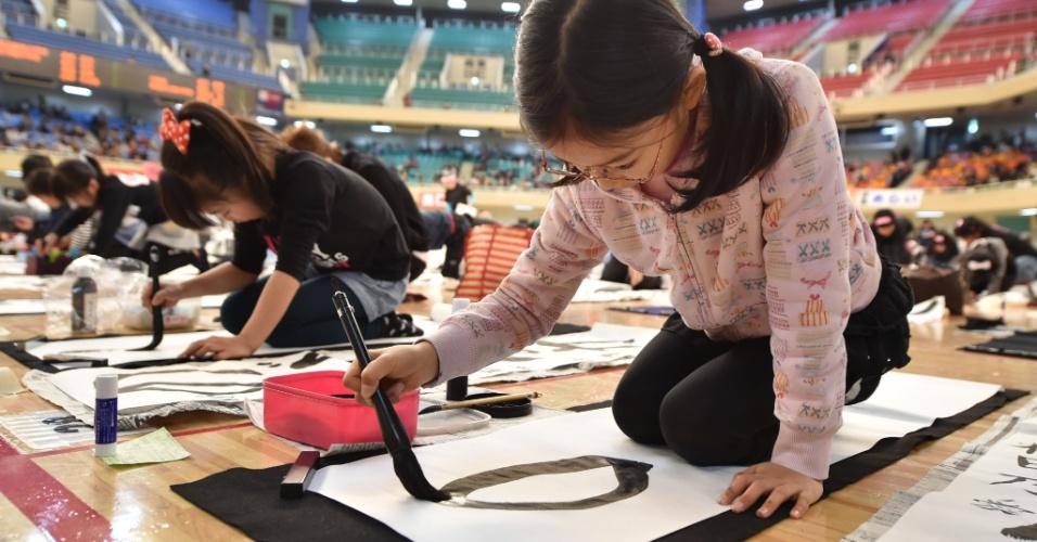 5.jan.2016 - Garota participa do concurso anual de caligrafia em Tóquio, no Japão. Cerca de 3.000 pessoas se inscreveram no evento, que faz parte das celebrações de Ano-Novo no país