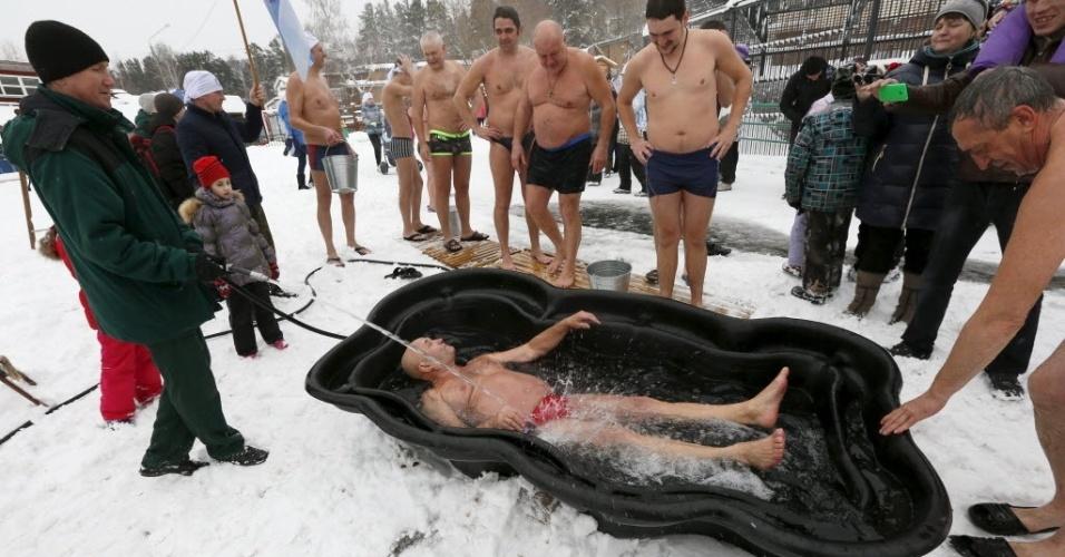 """6.jan.2015 - Mikhail Sashko, líder do clube siberiano de natação de inverno, se banha em água gelada durante um flash mob (manifestação relâmpago) em celebração do dia do Urso Polar no zoológico de Royev Ruchey, em Krasnoyarsk, na Rússia. """"Minha mulher diz que eu sou louco"""", diz Sashko. A temperatura no local na hora do banho de Sashko era de -5°C"""